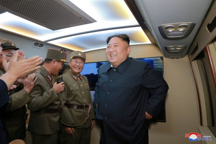 North Korean leader Kim Jong-un smiles as he guides missile testing at an unidentified location in North Korea, in this undated image provided by KCNA on Aug. 7. Reuters