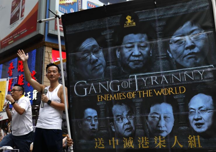 In this June 9, 2019, file photo, protesters display a banner with images of Chinese President Xi Jinping during a march along a downtown street against the proposed amendments to an extradition law in Hong Kong. AP