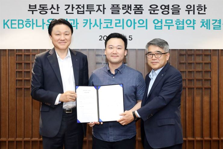 KEB Hana Bank's Deputy President and Chief Future Innovation Officer Han Jung-seong, left, poses with Kasa Korea CEO Yea Changwhan, center, and another Hana Bank official at the bank's headquarters in central Seoul, Monday, after they signed an agreement to cooperate on a digital platform for transaction of real estate trust certificates. Under the agreement, Kasa Korea will provide a platform to enable investors to make transactions of digital certificates for real estate trust. / Courtesy of KEB Hana Bank