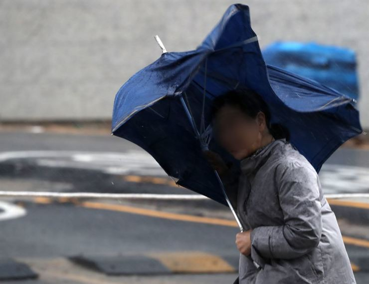 A woman struggles with gusting wind in Busan, Tuesday. Typhoon Francisco slammed the coastal city and other southern regions with torrential rain and thunderstorms. It weakened early Wednesday, leaving no major damage in the regions. Yonhap