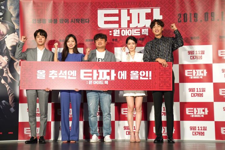 From left, actor Park Jung-min, actress Choi Yu-hwa, director Kwon Oh-kwang, actress Lim Ji-yeon, and actor Lee Kwang-soo pose holding a banner reading 'Give Your All to Tazza This Chuseok' at a media conference for the film 'Tazza: One-Eyed Jack,' held Thursday in Gwangjin-gu, Seoul. / Courtesy of Lotte Entertainment