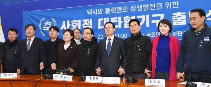 Minister of Land, Infrastructure and Transport Kim Hyun-mee, fourth from left, and Kakao Mobility CEO Jung Joo-hwan, third from left, hold hands with representatives from the taxi industry during a ceremony to launch a panel to seek mutual growth between conventional taxi service providers and ride-hailing platform operators at the National Assembly on Jan. 22. / Korea Times photo by Oh Dae-geun