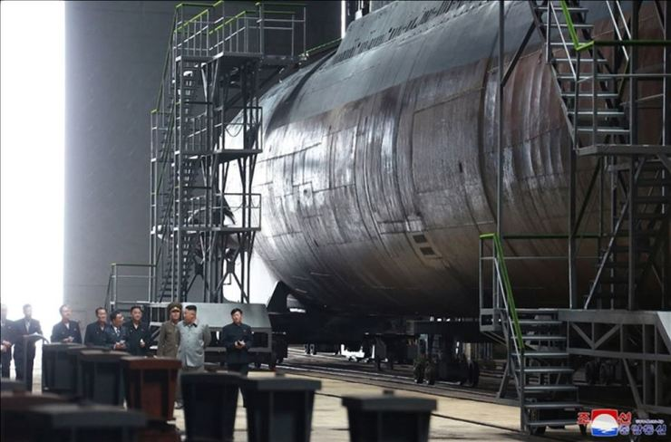 North Korean leader Kim Jong-un and his aides watch the country's new submarine under construction, according to the state's Korean Central Television, July 23. Yonhap