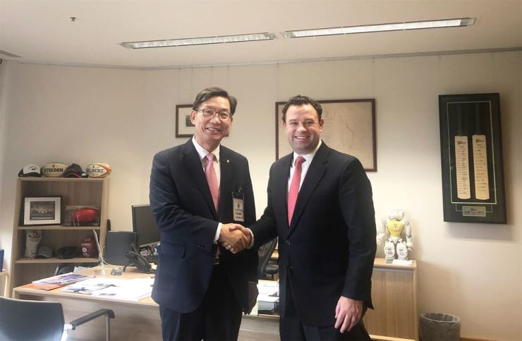 NongHyup Bank CEO Lee Dae-hoon shakes hands with Stuart Laurence Ayres, New South Wales Minister for Jobs, Investment and Tourism, at the minister's office Aug. 22 (local time). Courtesy of NongHyup Bank