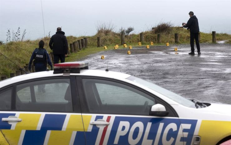 Police collect and photograph evidence in the carpark of the Te Toto Gorge lookout on Whaanga Rd, south of Raglan, New Zealand, Friday, Aug. 16, 2019. A manhunt was underway in New Zealand after an Australian tourist was killed following what police believe was a random attack on the van that he and his partner were sleeping inside. AP