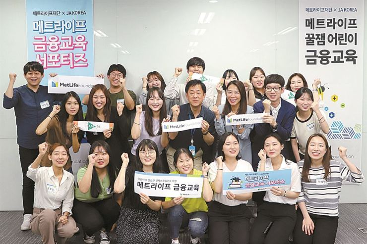 University students volunteering to teach finance to children pose with MetLife Korea employees at the company in southern Seoul, in this photo taken in June. Around 1,300 elementary school students took part in the sessions organized by the MetLife Korea Foundation in June and July. Courtesy of MetLife Korea