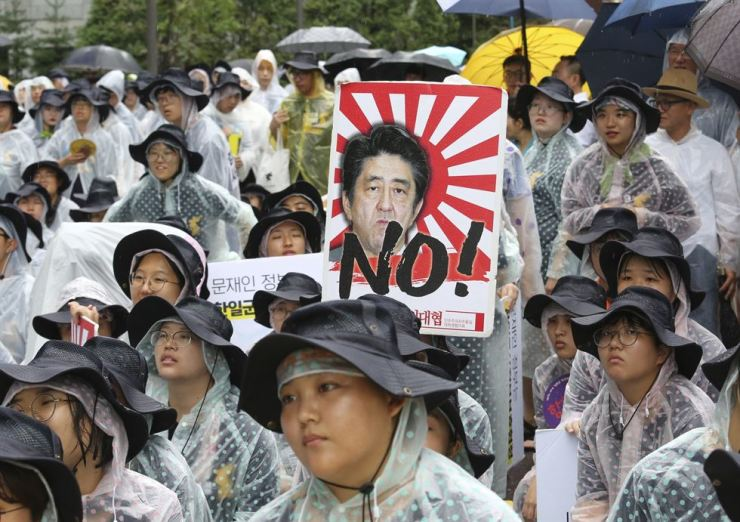 Korean protesters with an image of Japanese Prime Minister Shinzo Abe attend a rally to mark the Korean Liberation Day from Japanese colonial rule, in front of the Japanese Embassy in Seoul, Thursday. AP