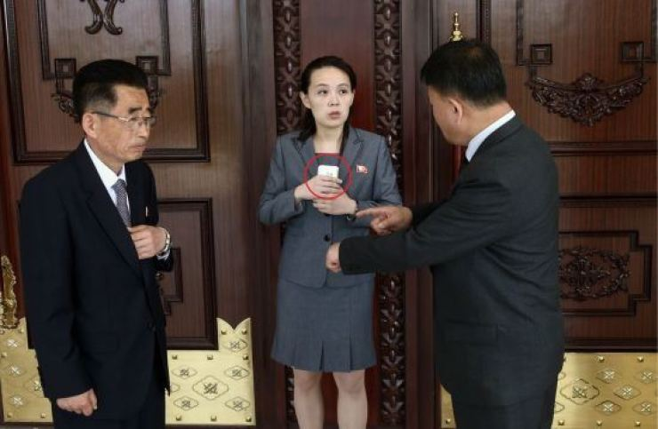 North Korean leader Kim Jong-un's younger sister Kim Yo-jong is seen with a mobile phone in this undated file photo. With over 600,000 mobile phone users, phone scams are spreading across the North. / Yonhap