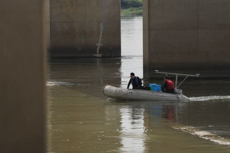 Police officers under Magok Bridge in Goyang, Gyeonggi Province, Wednesday, search for body parts of a man whose dismembered torso was found earlier. The suspect surrendered himself on Saturday. / Yonhap