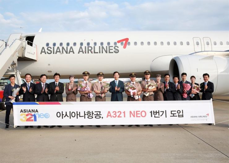 Asiana Airlines President Han Chang-soo, center, and other airline staff poses in front of the country's first A321 NEO at Incheon International Airport, Thursday. The aircraft is scheduled to service on short- to mid-range routes from September. Courtesy of Asiana Airlines