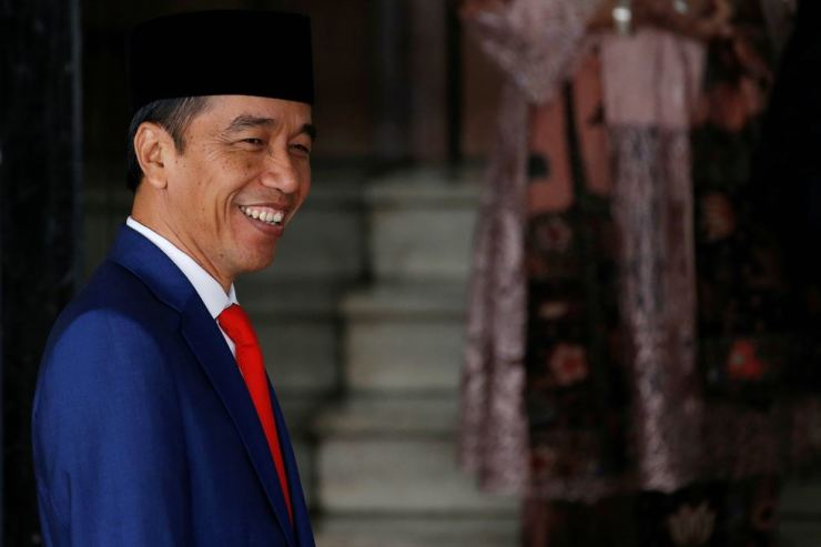 Indonesian President Joko Widodo smiles at reporters as he arrives before delivering a speech ahead of Independence Day, at the parliament building in Jakarta, Indonesia, Aug. 16, 2019. Reuters
