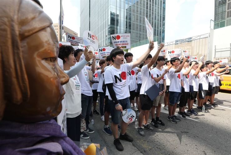 High school students hold up 'Japan boycott' signs during a news conference to declare their participation in a widening civic campaign of boycotting Japanese products in front of the Japanese Embassy in Seoul, Friday. Korea Times file