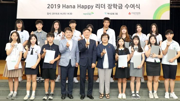 Hana Financial Group's Chief Financial Officer Lee Seung-yeol, front row fifth from left, poses with officials of charity organizations and students at an event awarding student scholarships at the bank's headquarters in central Seoul, Thursday. The scholarships are provided for underprivileged students with outstanding grades or talent in art or sports. / Courtesy of Hana Financial Group