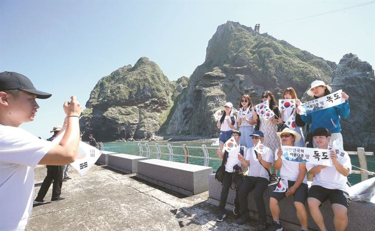 Visitors pose at Dokdo, Tuesday, as Typhoon Krosa is advancing north toward Japan. On National Liberation Day, the large typhoon is expected to sweep through Japan, placing the nation's easternmost islets under its influence. / Yonhap