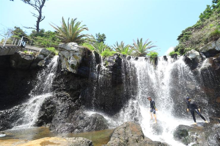 Summer vacationers cool off under a waterfall in Seogwipo, Jeju Island, Wednesday. Hot weather is expected across the country for a while after Typhoon Francisco weakened and passed across the country the previous day. / Yonhap