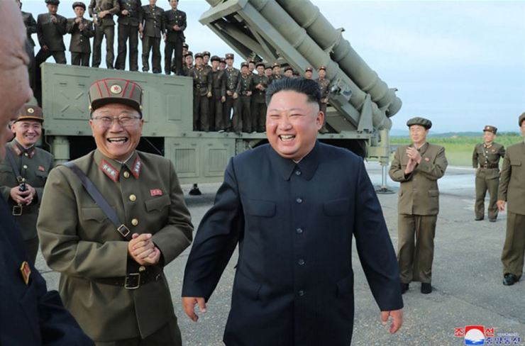 North Korean leader Kim Jong-un smiles after observing a test of what the North said is a 'super-large multiple rocket launcher' on Saturday when it fired two short-range projectiles off its eastern coast. Yonhap
