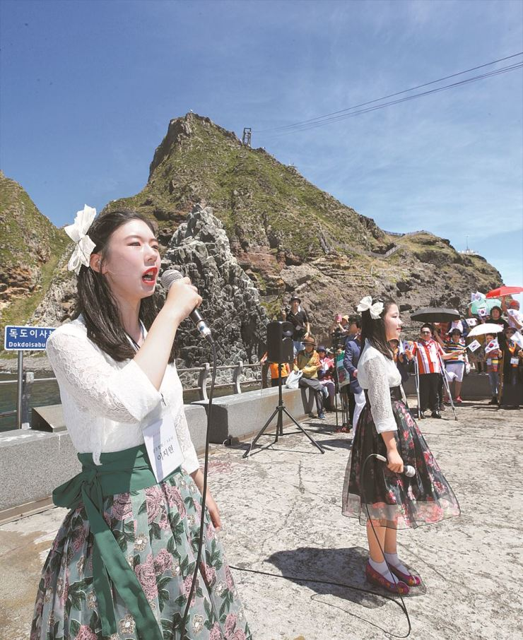 Participants of the 2019 Ulleungdo-Dokdo International Association Disabled Culture Expo sing 'Arirang,' the nation's iconic folk song, at the easternmost islets of Dokdo, Tuesday. The event was hosted by the International Association of Culture Exchange for Disabled. / Yonhap