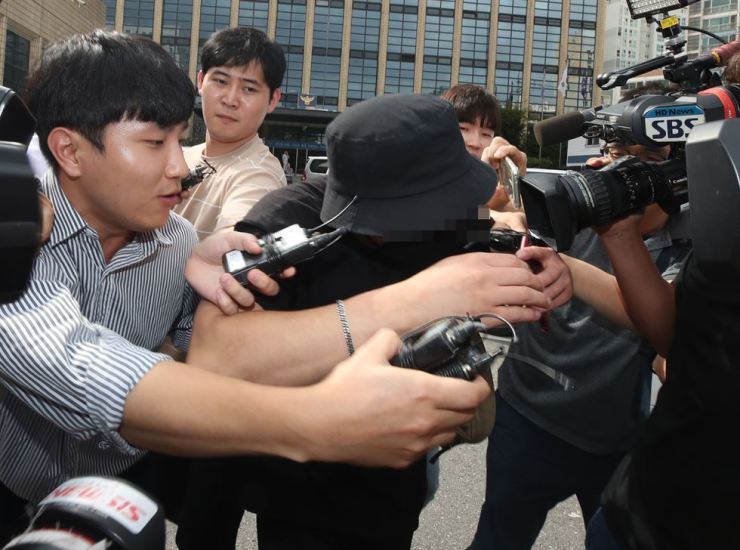 A Korean man, center, suspected of assaulting a Japanese woman is surrounded at Mapo Police Station in Seoul, Saturday. /Yonhap