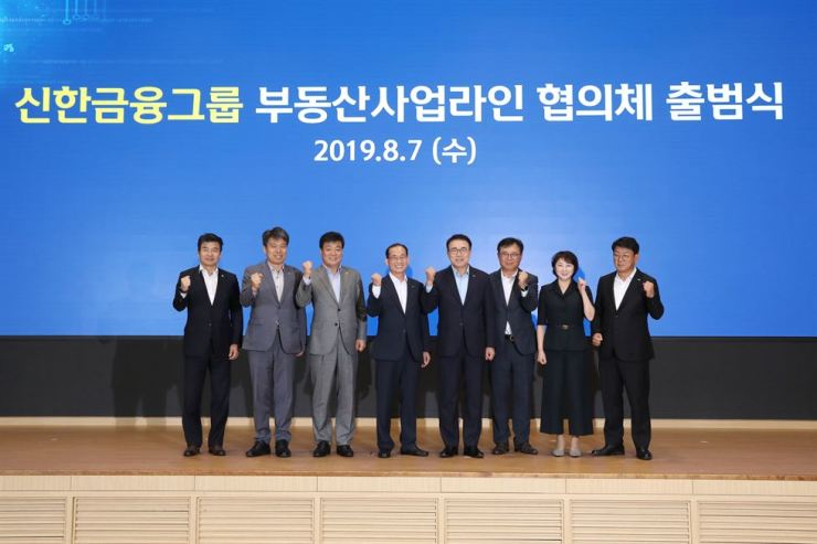 Shinhan Financial Group Chairman Cho Yong-byoung, fourth from right, and company executives gather during a ceremony at the group's headquarters in Seoul, Wednesday. The ceremony celebrated the launch of a consultative body for the group's real estate businesses. / Courtesy of Shinhan Financial Group