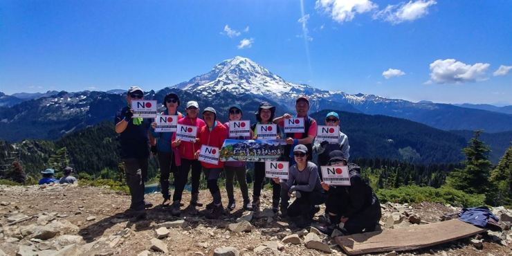 Members of the Seattle Evergreen Hiking Club hold up a ''No Japan'' sign on Mount Rainier in Seattle. Courtesy of Seattle Evergreen Hiking Club