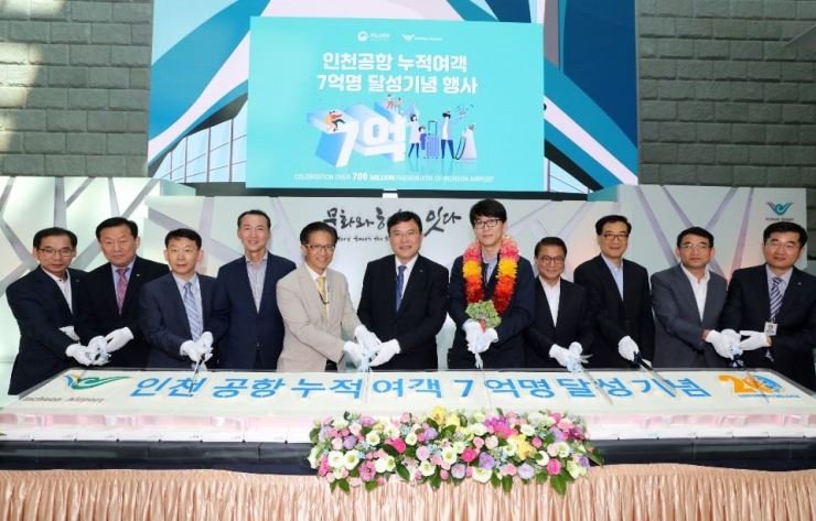 IIAC President Koo Bon-hwan, center, cuts a giant rice cake celebrating the 700 million passenger mark with airport officials at Incheon International Airport, Wednesday. Courtesy of IIAC