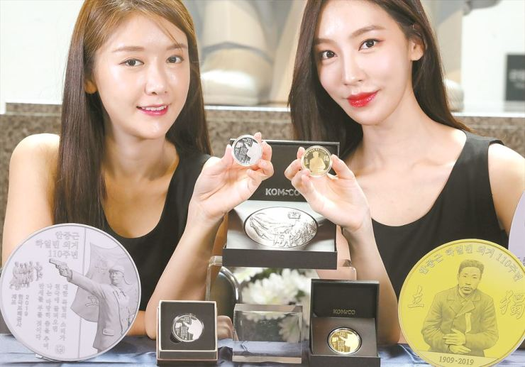 Models promote medals designed to commemorate the 110th anniversary of the patriotic deed of Ahn Jung-geun, who was martyred for the country, at the Patriot Ahn Jung-geun Memorial Hall in central Seoul, Friday. Ahn, a revered independence hero, assassinated a prominent Japanese colonial leader at Harbin Station in 1909. / Yonhap