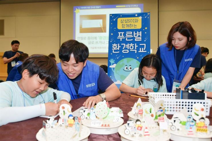 Samsung SDI employees and children engage in an environmental protection class at Kyowon Dream Center in Gyeongju, North Gyeongsang Province, in this photo provided by the company, Wednesday. / Courtesy of Samsung SDI