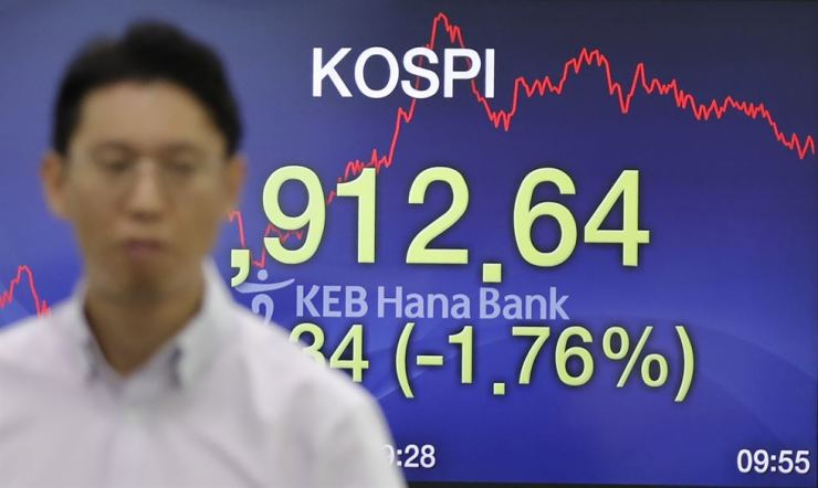 A currency trader walks by the screen showing the Korea Composite Stock Price Index at the foreign exchange dealing room in Seoul, Korea, Tuesday, Aug. 6, 2019. AP