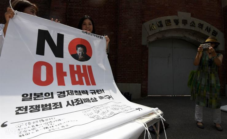 A Japanese tourist, second from left, holds up a 'No Abe' banner with a Korean civic activist after leaving a message of protest to Japanese Prime Minister Shinzo Abe on the banner, in front of Seodaemun Prison History Hall in Seoul, Thursday. / Korea Times photo by Seo Jae-hoon