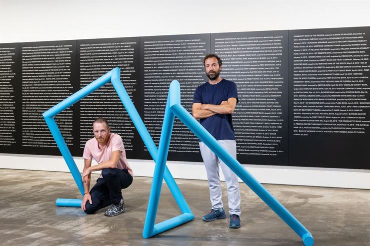 Jakob Fenger, left, and Bjornstjerne Christiansen of Superflex pose in front of 'Bankrupt Banks, October 30, 2013' at Kukje Gallery Busan. Courtesy of Kukje Gallery
