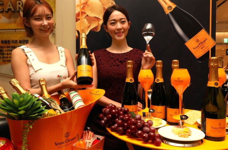 Models promote French champagne Veuve Clicquot at the Shinsegae Department Store in downtown Seoul, Sunday. The department store is carrying out an event offering special discounts of up to 80 percent for premium champagne and wine produced by global brands until Aug. 18. / Yonhap