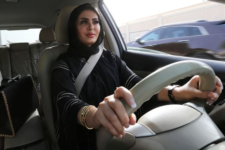 In this June 24, 2018, file photo, Huda al-Badri, 30, poses behind a steering wheel of a car in the early morning hours when the royal decree lifted the ban on women driving a car in Saudi Arabia, in Riyadh, Saudi Arabia. The country will also allow women to travel alone without the approval of their guardian once they are 21 years old. EPA
