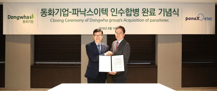 Dongwha Enterprise CEO Kim Hong-jin, left, and JKL Partners CEO Jung Jang-geun shake hands during an event celebrating Dongwha's acquisition of Panax Etec, a secondary battery material maker in which JKL Partners had the largest stake, at Dongwha Enterprise's headquarters on Yeouido, Seoul, Wednesday. Courtesy of Dongwha Enterprise
