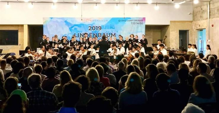 The Lindenbaum Festival Orchestra and the U.S. National Children's Chorus perform together during the 2019 Lindenbaum Festival held at an old military building which used to be a bowling alley for soldiers in Camp Greaves in Paju, northern Gyeonggi Province, July 13. Located near the Demilitarized Zone, Camp Greaves had served as a base for the 506th U.S. Second Infantry Division for about 50 years after the Korean Armistice Agreement that ended the 1950-53 Korean War, before being returned to the South Korean government in 2007. Courtesy of Lindenbaum Organization