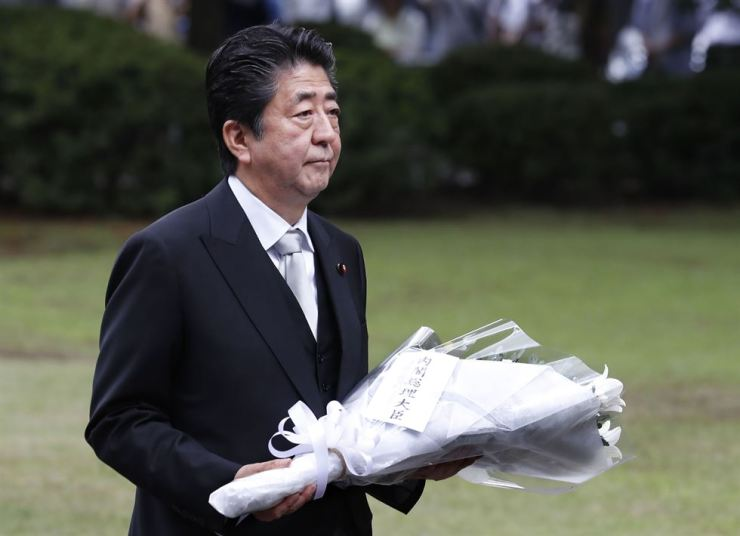 Japanese Prime Minister Shinzo Abe carries a bouquet of flowers to offer at the Chidorigafuchi National Cemetery for unidentified remains of the nation's war dead in Tokyo, Thursday, Aug. 15, 2019. Japan marked Thursday the 74th anniversary of the end of the World War II. AP-Yonhap