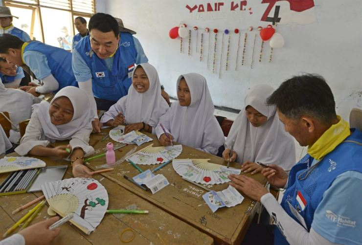 POSCO employees demonstrate how to make a traditional Korean fan at Ai-Hidaya High School in Cilegon, Indonesia, during their volunteer service program in the city from Aug. 17 to 24. Courtesy of POSCO