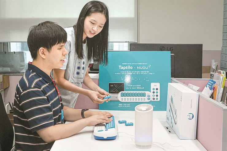A blind person tries to learn braille with Taptilo, a braille educating device that uses SK Telecom's Nugu voice-activated AI speaker. / Courtesy of SK Telecom