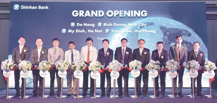 Shinhan Bank CEO Jin Ok-dong, sixth from right, Shinhan Bank Vietnam's General Director Shin Dong-min, first from left, alongside officials from the Southeast Asian country cut a tape at an opening ceremony of the bank's four new branches there, Aug. 15. Courtesy of Shinhan Bank