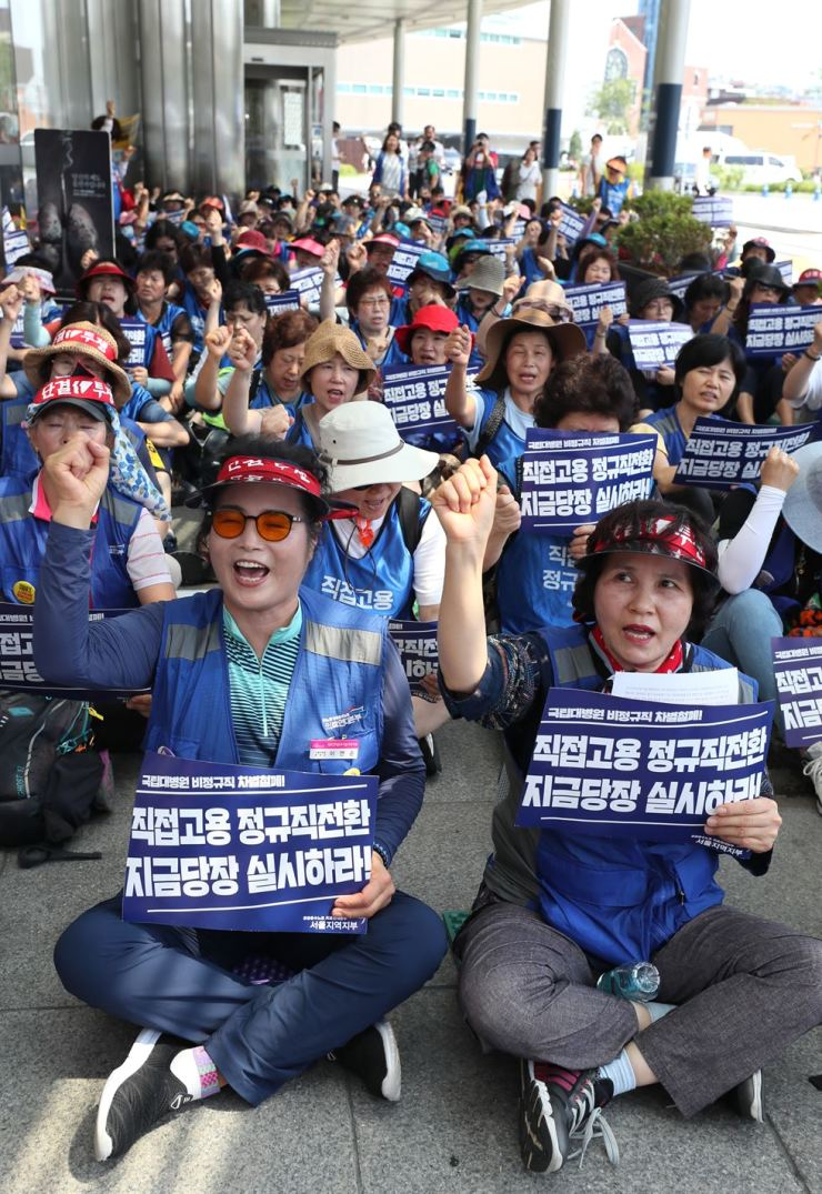 Temporary workers at Seoul National University Hospital stage a rally in front of the hospital in Seoul, Thursday, launching an indefinite strike, calling for the hospital management to hire them as full-time workers. Yonhap