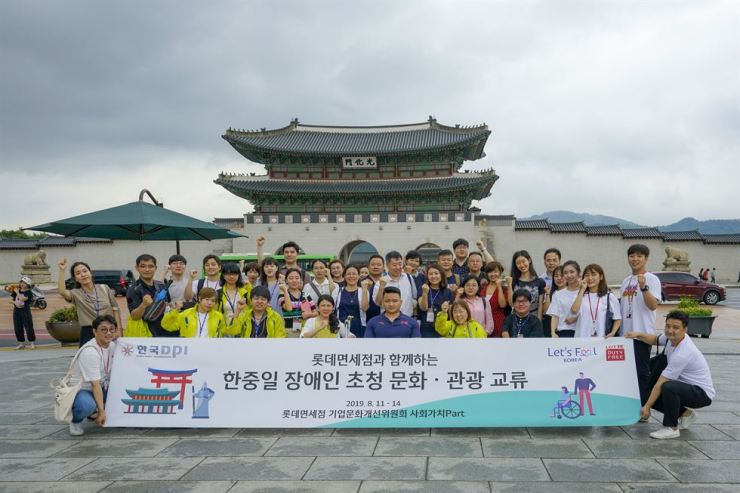 Korean, Chinese and Japanese youths with disabilities pose for a group photo in front of Gyeongbok Palace in Seoul, Aug. 14. / Courtesy of Lotte Duty Free