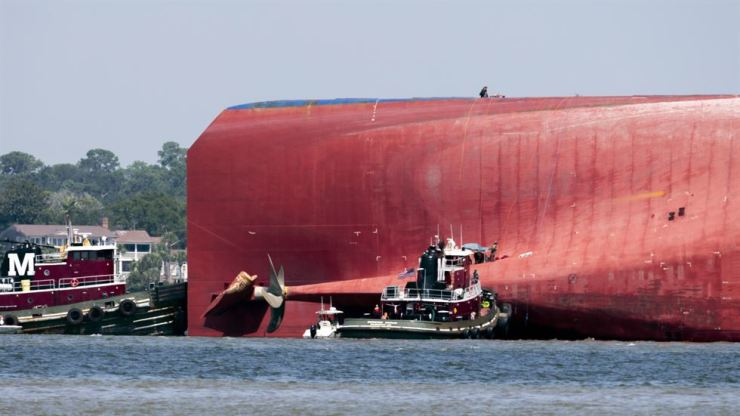 Rescuers work near the stern of the vessel Golden Ray as it lays on its side near the Moran tug boat Dorothy Moran, Monday, Sept. 9, 2019, in Jekyll Island, Ga. Coast Guard rescuers have made contact with four Korean crew members trapped inside the massive cargo ship off the coast of Georgia. AP