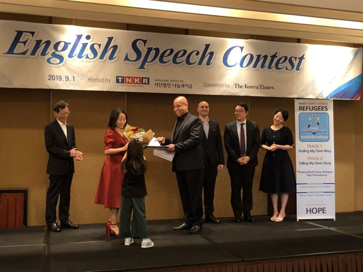 The winner of TNKR's English Speech Contest receives prizes from TNKR co-founder Casey Lartigue at the Grand Hyatt Seoul, Sept. 1. / Courtesy of TNKR