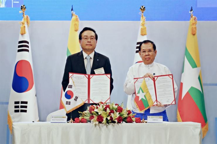 Woori Financial Group Chairman Sohn Tae-seung, left, holds an MOU with U Zaw Min Win, chairman of the Union of Myanmar Federation of Chambers of Commerce and Industry, during the Korea-Myanmar Business Forum in Yangon, Myanmar, Wednesday. Under the deal, the two parties will work together to help Korean firms enter into the Southeast Asian country. / Courtesy of Woori Financial Group