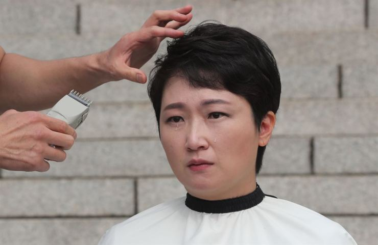Rep. Lee Un-ju shaves her head on the street of Seoul, Tuesday, to protest against the appointment of new Justice Minister Cho Kuk. Yonhap
