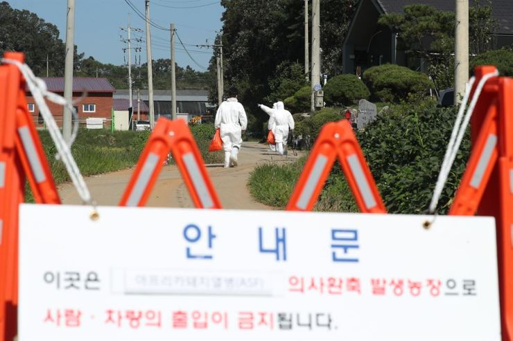 Quarantine officials head to a pig farm in Yeoncheon, Gyeonggi Province, where the second case of African swine fever was confirmed on Wednesday. The sign reads: 'African swine fever was found on this farm and  entrance for all personnel and vehicles is banned.' Yonhap