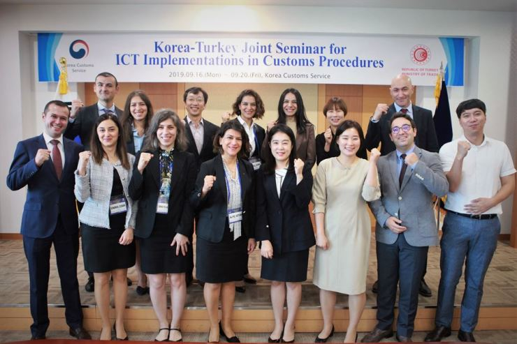 Aliye Ozturk, fourth from left in the front row, clenches her fist with customs officials from Turkey and the Korea Customs Service (KCS) at the Seoul main office of the KCS, Sept 17. Courtesy of KCS