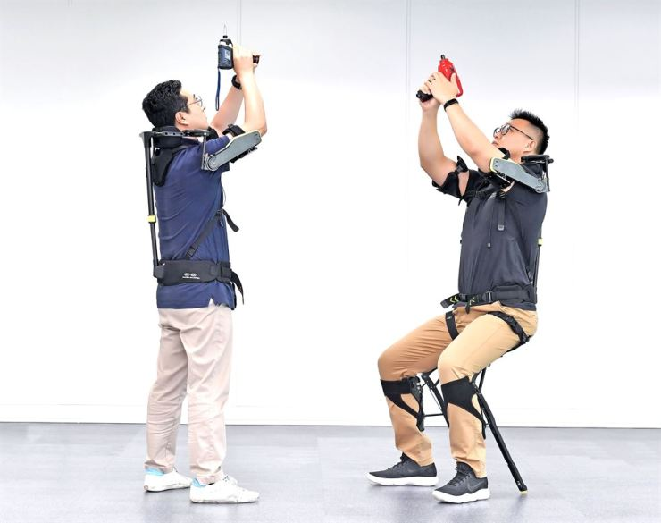 Workers test Hyundai Motor Group's newly developed wearable robot called VEX. / Courtesy of Hyundai Motor Group