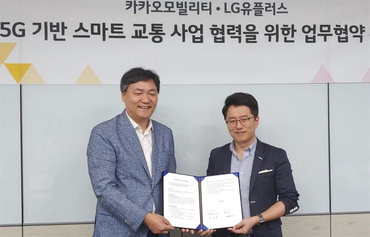 Choi Soon-jong, left, who heads the corporate infrastructure business group at LG Uplus, poses for a photo with Ryu Gung-seon, co-CEO of Kakao Mobility, at the mobile carrier's head office in Seoul, Sunday, after signing an MOU to cooperate in developing smart mobility services. / Courtesy of LG Uplus