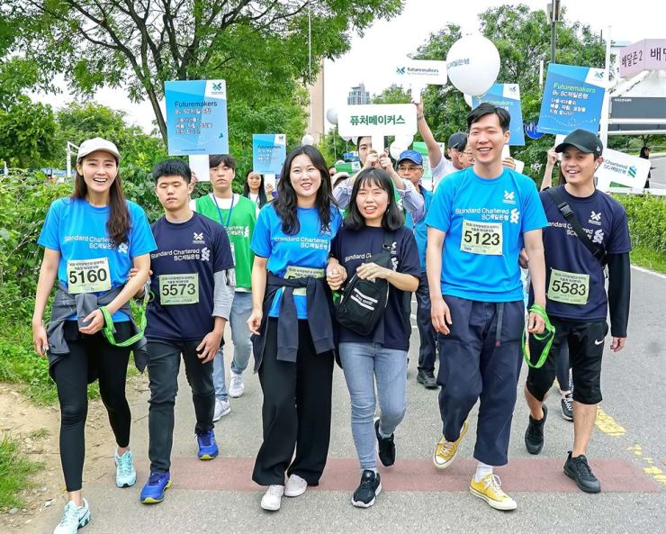 Standard Chartered (SC) Bank Korea employees walk with blind people in Yeouido Hangang Park, Seoul, Saturday, to participate in a marathon as their guide runners. The bank has participated in the race annually since 2015 to raise awareness about visual impairment. / Courtesy of SC Bank Korea