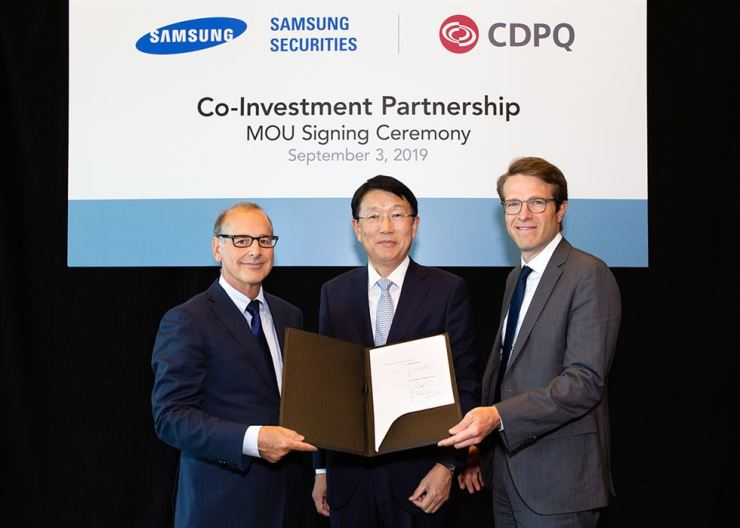 Samsung Securities CEO Chang Seok-hoon, center, poses with Claude Bergeron, left, and Emmanuel Jaclot, two senior executives at Caisse de Depot et Placement du Quebec (CDPQ) after signing a memorandum of understanding (MOU) at the CDPQ Montreal office in Canada, Sept. 3 (local time). The two firms agreed to boost cooperation in seeking joint investment opportunities for Korean institutional investors in North America and Europe. CDPQ, one of the world's largest institutional investors, specializes in real estate, private equity and infrastructure investments. Courtesy of Samsung Securities